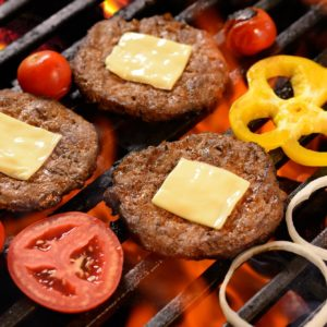 Grilled meat/burger with cheese on top and vegetable on the flaming grill